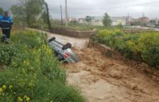 Un vehicle és arrossegat per l'aigua de la riera de La Canonja