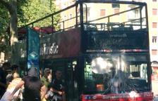Dos encapuchados tiran pintura contra un bus turístico en la plaza Kennedy de Barcelona